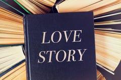 Vecchi libri dalla copertina rigida con il libro Love Story sulla cima fotografia stock libera da diritti