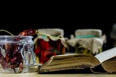 Vecchi libri e spezie Peperoni secchi e ricette Vecchia tabella di cucina Immagini Stock