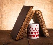 Vecchi libri e tazza con molti cuori rappresentati sui vecchi tum di legno Immagine Stock