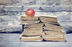 Vecchi libri Mucchio di vecchi libri e di una mela rossa Immagini Stock