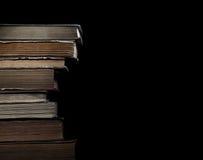 Vecchi libri in mucchio su un fondo nero Fotografia Stock Libera da Diritti