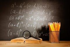 Vecchi libri scolastici lente e matite che si trovano su uno scrittorio di legno della scuola davanti ad una lavagna nera con le  Immagini Stock