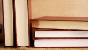 Vecchi libri in una copertura di cuoio su uno scaffale di legno archivi video