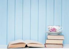 Vecchi libri, vetri e tazza di antiquariato della porcellana sullo scaffale per libri Fotografia Stock