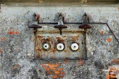 Vecchi, linea di energia elettrica e fusibili arrugginiti su una vecchia casa fotografia stock