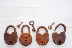 Vecchi lucchetti arrugginiti e chiavi su un fondo di legno Fotografia Stock