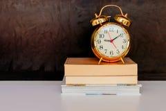 Vecchi oro e libro d'annata della sveglia sopra bianco su fondo nero con lo spazio della copia aggiunga il testo immagini stock