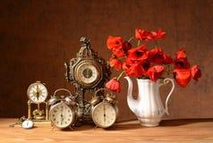 Vecchi orologi e redpoppies in un vaso Immagine Stock