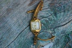 Vecchi orologi gialli consumati su una tavola grigia immagini stock