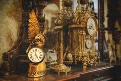 Vecchi orologio ed utensile d'annata del bronzo dell'oggetto d'antiquariato sullo scaffale di legno Fotografia Stock
