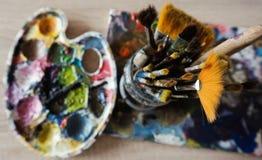 Vecchi pennelli con una tavolozza della pittura fotografie stock libere da diritti