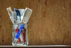 Vecchi pennelli sul fondo di legno urgente del pannello Immagini Stock Libere da Diritti