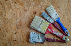 Vecchi pennelli sul pannello di legno urgente Immagine Stock Libera da Diritti