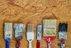 Vecchi pennelli sul pannello di legno urgente Fotografie Stock Libere da Diritti