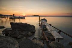 Vecchi pilastro, barca e tramonto delle rocce Fotografie Stock Libere da Diritti