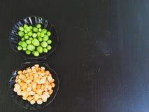 Vecchi piselli gialli con i piselli freschi in piatti Fotografia Stock