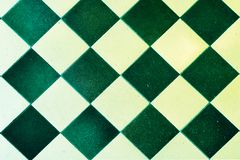Vecchi quadrati verdi e bianchi delle piastrelle per pavimento, immagine stock