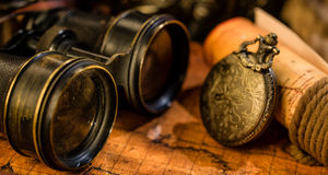 Vecchi retro bussola e binocolo d'annata sulla mappa di mondo antica Immagine Stock