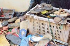Vecchi rifiuti della scarpa allora non utilizzati a sinistra nel canestro Immagini Stock