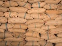 Vecchi sacchi della canapa impilati in una fila Immagini Stock Libere da Diritti
