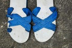 Vecchi sandalo di gomma inutilizzato con lo strappo e lacerato fotografie stock