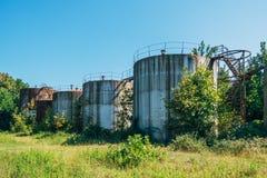 Vecchi serbatoi dell'olio abbandonati arrugginiti con le scale invase dagli alberi immagini stock libere da diritti
