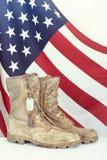 Vecchi stivali e medagliette per cani di combattimento con la bandiera americana Immagini Stock