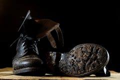 Vecchi stivali militari fangosi Colore nero, sogliole sporche Tabella di legno Fotografie Stock Libere da Diritti