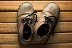 Vecchi stivali sul pavimento di legno Fotografia Stock