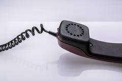 Vecchi telefono e cavo sulla tavola bianca con la riflessione Immagini Stock Libere da Diritti