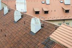 Vecchi tetti rossi con le mattonelle ed i camini bianchi a Praga fotografie stock