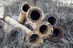 Vecchi tubi per fognatura arrugginiti dell'acqua nell'erba asciutta alta Fotografie Stock