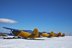 Vecchi velivoli, parcheggiati con neve in giorno pieno di sole immagini stock libere da diritti