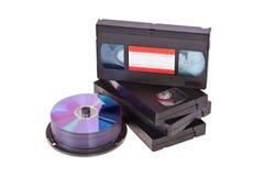 Vecchi video nastri a cassetta con un disco di DVD isolato Fotografie Stock