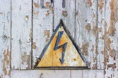 Vecchia alta tensione del pericolo del segno contro lo sfondo di vecchio woode Immagini Stock Libere da Diritti