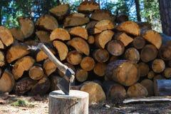 Vecchia ascia che sta contro i pezzi accatastati di legna da ardere Immagini Stock