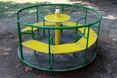 Vecchia attrezzatura pubblica all'aperto variopinta del campo da giuoco fatta di metallo e di legno nella forma della rotonda cir immagine stock libera da diritti