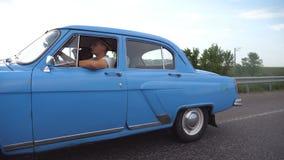 Vecchia automobile classica che viaggia sulla strada principale il giorno di estate Giovani coppie che guidano sulla strada campe stock footage