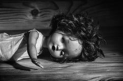 Vecchia bambola tagliata su una tavola di legno Immagini Stock