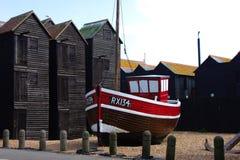 Vecchia barca del pescatore sulla spiaggia di Hastings con le capanne del pescatore nei precedenti immagini stock libere da diritti