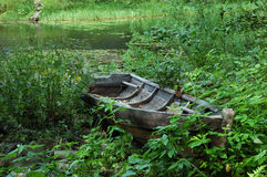 Vecchia barca di legno in erba sulla banca del lago Immagini Stock