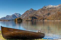 Vecchia barca a remi di legno marrone su una riva del lago della montagna nelle alpi svizzere Fotografie Stock Libere da Diritti