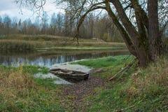 Vecchia barca sulla catena del fiume legata ad un albero immagini stock