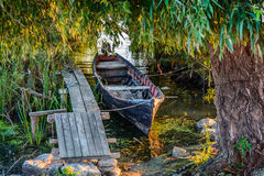 Vecchia barca sulla costa vicino al molo Paesaggio rustico con il bacino di legno nella sera di estate Immagini Stock Libere da Diritti