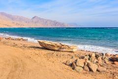 Vecchia barca sulla spiaggia, montagne nei precedenti Fotografia Stock