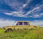 Vecchia berlina di modello in nuvole del cielo dell'erba Immagini Stock