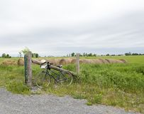 Vecchia bici che pende contro un recinto di legno della posta su un'azienda agricola immagini stock libere da diritti