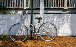Vecchia bicicletta bianca incatenata per inverdirsi Palo Immagine Stock
