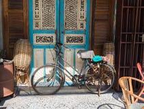 Vecchia bicicletta che pende contro il granaio grungy in Tailandia immagini stock
