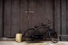 Vecchia bicicletta che pende contro le vecchie porte di legno Con una carta marrone immagini stock